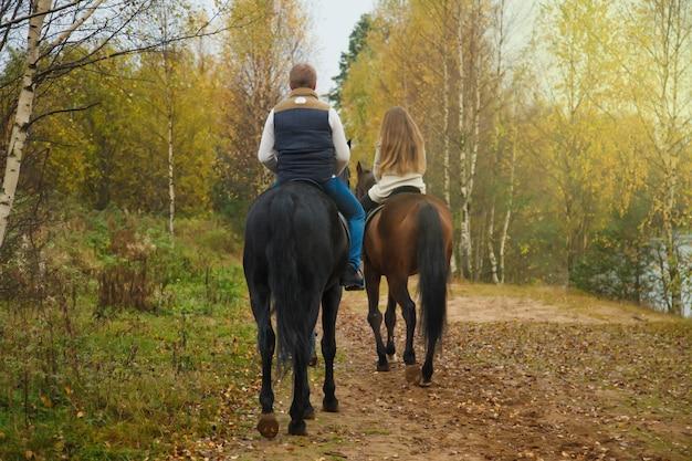 Joli jeune couple à cheval dans la forêt d'automne sur route de campagne. cavaliers en automne park par mauvais temps nuageux avec pluie légère. concept d'équitation en plein air, de sports et de loisirs. espace de copie