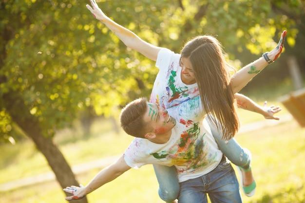 Joli jeune couple faisant un avion ou un avion. belle fille et bel homme s'amuser en plein air. se regarder