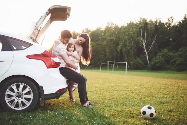 Joli jeune couple marié et leur fille se reposent dans la nature. la mère, le père et la petite fille sont assis sur le coffre de voiture ouvert