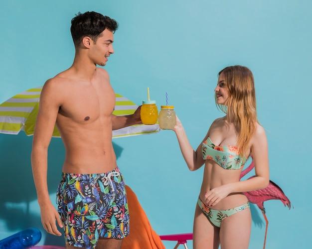 Joli jeune couple se reposant avec des cocktails en studio