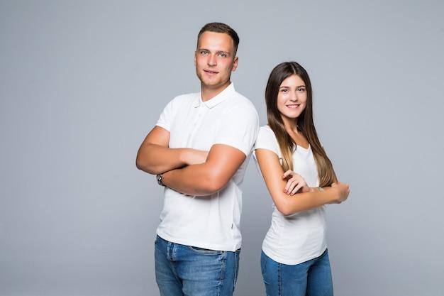 Joli jeune couple souriant étudiants studio isolé t-shirts blancs jeans câlins