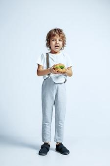 Joli jeune garçon bouclé dans des vêtements décontractés sur blanc