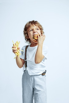 Joli jeune garçon bouclé dans des vêtements décontractés sur un mur blanc. manger un hamburger avec des pommes de terre frites. enfant d'âge préscolaire masculin de race blanche avec des émotions faciales lumineuses. enfance, expression, amusement, restauration rapide.