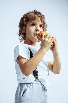 Joli jeune garçon bouclé dans des vêtements décontractés sur un mur blanc. manger des hamburgers. enfant d'âge préscolaire masculin de race blanche avec des émotions faciales lumineuses. enfance, expression, s'amuser, restauration rapide. rêveur.