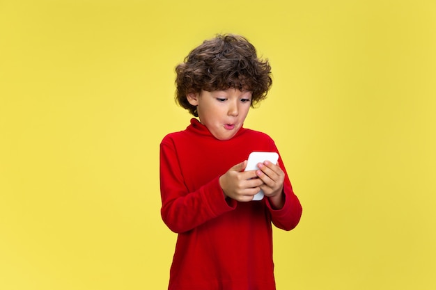 Joli jeune garçon bouclé en vêtements rouges sur l'amusement de l'expression de l'enfance du mur jaune