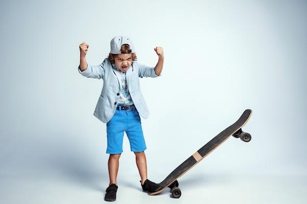 Joli jeune garçon sur planche à roulettes dans des vêtements décontractés sur blanc