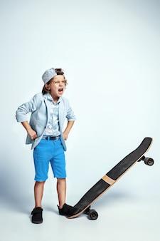 Joli jeune garçon sur planche à roulettes dans des vêtements décontractés sur le mur blanc du studio