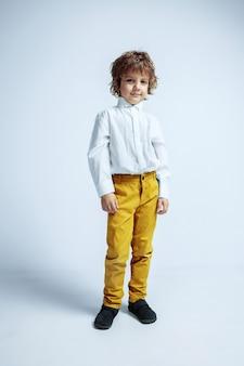 Joli jeune garçon en vêtements décontractés sur le mur blanc du studio