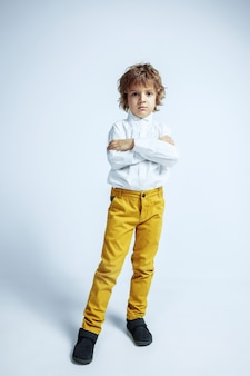 Joli jeune garçon en vêtements décontractés sur mur blanc. pose à la mode. enfant d'âge préscolaire masculin caucasien avec des émotions faciales lumineuses. enfance, expression, plaisir. posant les mains croisées.