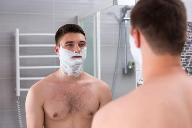 Joli jeune homme avec de la mousse à raser sur les joues debout devant un miroir dans la salle de bains carrelée moderne à la maison