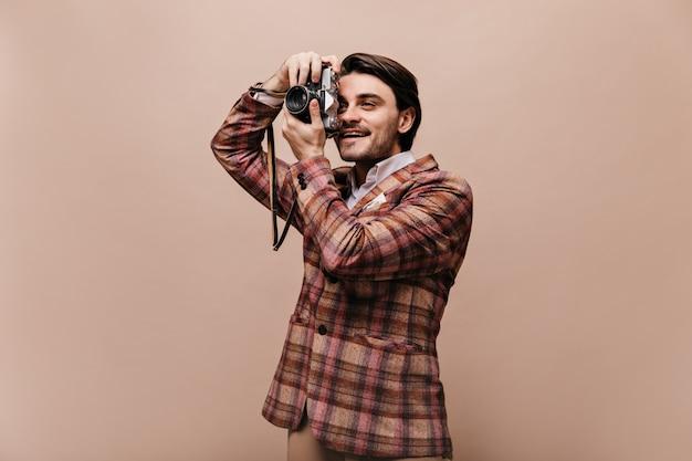 Joli jeune photographe aux cheveux bruns, en veste à carreaux tendance faisant des photos et souriant