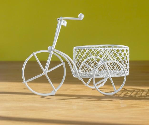 Joli jouet de vélo rétro avec panier sur un bureau en bois sur des vibrations estivales de mur jaune