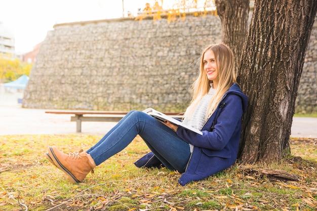 Joli modèle assis arbre incliné et lecture