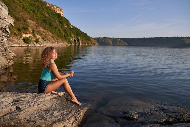 Joli modèle assis sur la rive du lac