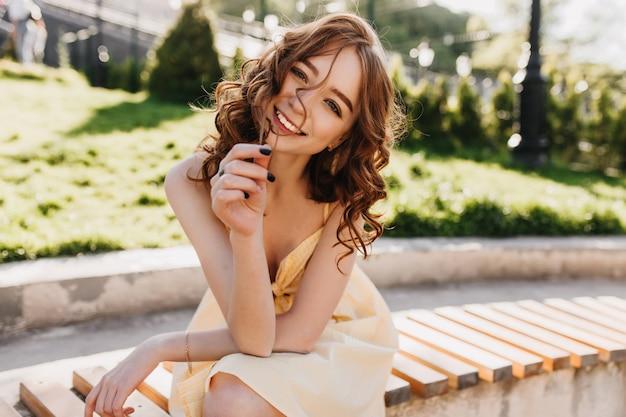 Joli modèle féminin aux cheveux roux ondulés assis sur un banc de parc. photo extérieure d'une fille au gingembre heureuse en robe jaune posant sur la nature.