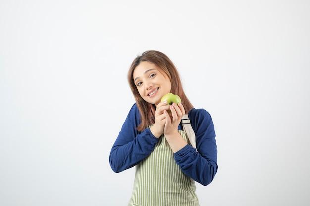 Un joli modèle de jeune fille en tablier tenant une pomme verte fraîche.