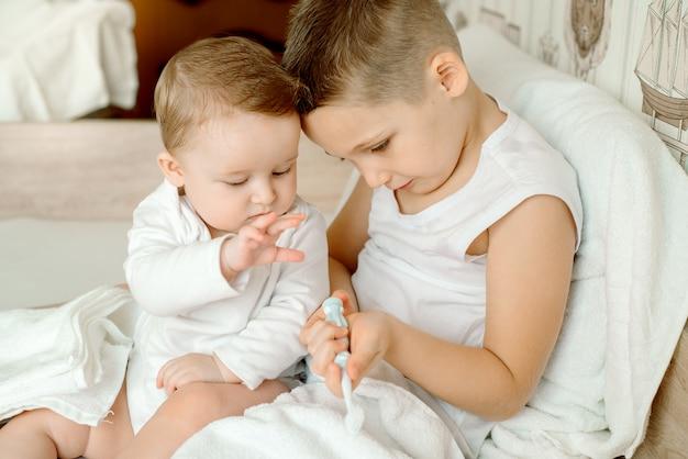 Joli petit bébé dans une serviette à capuche à la main après le bain
