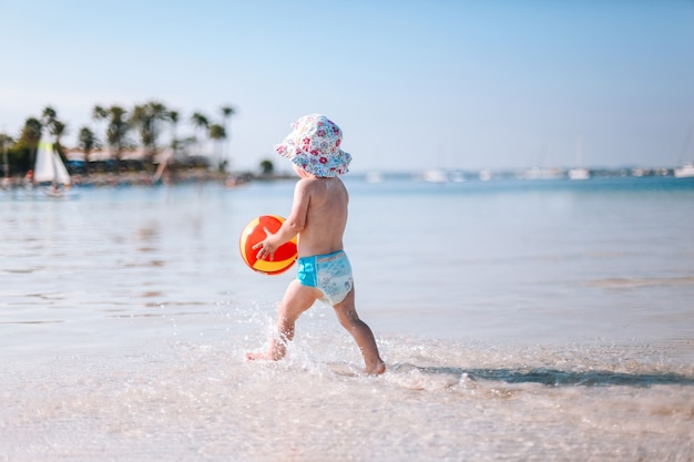 Joli petit bébé frisé joue avec une balle colorée sur la plage. petite fille marchant sur l'eau au bord de la mer.
