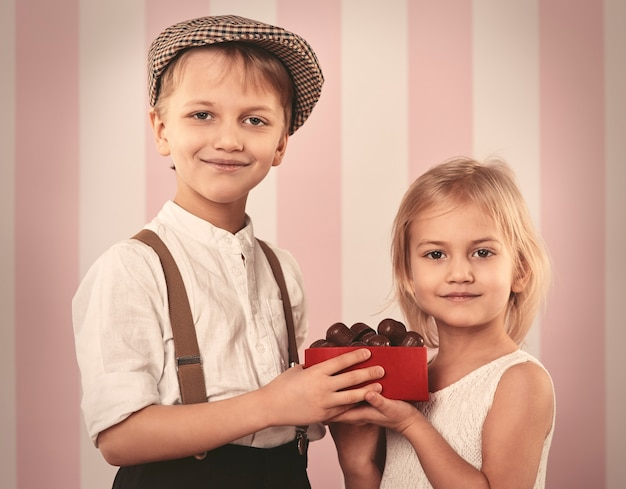 Joli petit couple tenant une boîte avec praline