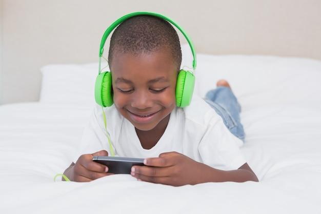 Joli petit garçon à l'aide de smartphone et de la musique au lit
