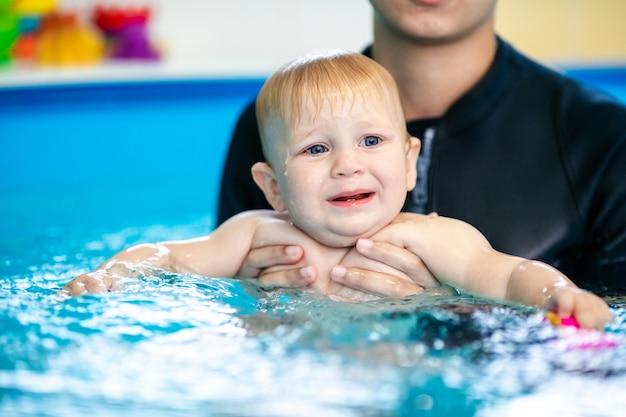 Joli petit garçon apprenant à nager dans une piscine spéciale pour les petits enfants