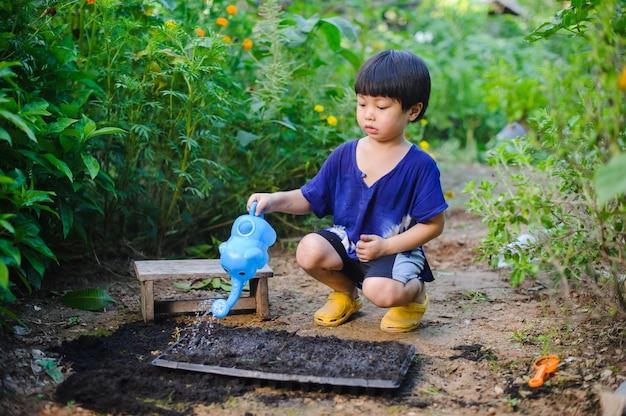 Joli petit garçon arrosant des plantes avec un arrosoir dans le jardin