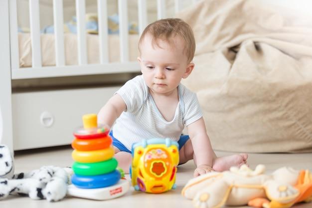 Joli petit garçon assemblant une tour de jouets colorée sur le sol