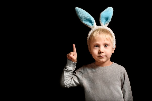 Joli petit garçon blond aux oreilles de lièvre montre son index se lève vers le haut sur fond noir