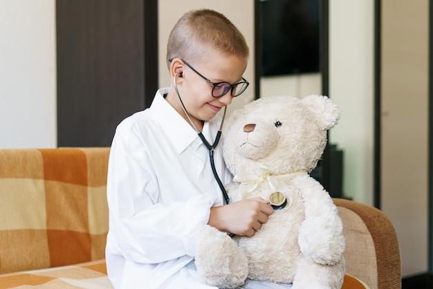Joli petit garçon caucasien jouant à un jeu amusant comme un docteur tenant un stéthoscope écoutant des enfants d'âge préscolaire...