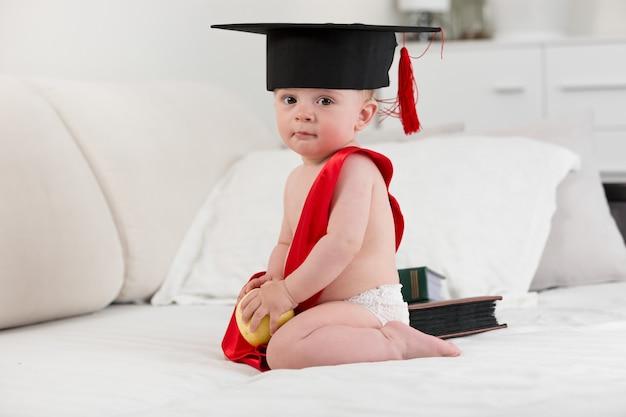 Joli petit garçon en chapeau de graduation tenant une pomme. concept d'éducation de bébé