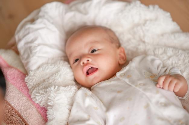 Joli petit garçon dans une chambre à la lumière blanche le nouveau-né est mignon. dans la literie pour les enfants nés - images