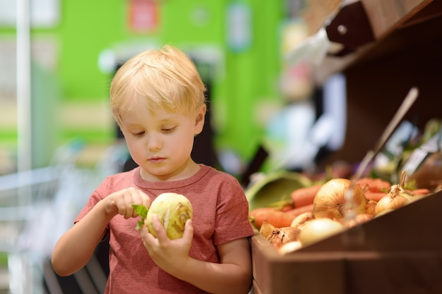Joli petit garçon dans un magasin d'alimentation ou un supermarché choisissant des racines de céleri bio fraîches