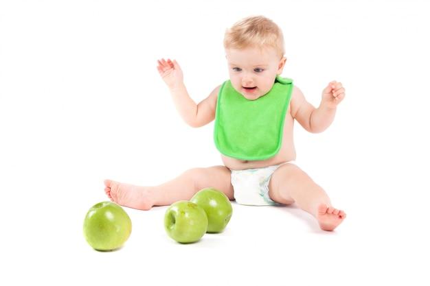 Joli petit garçon heureux dans le bavoir vert joue aux pommes