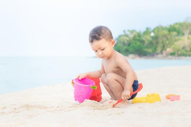 Joli petit garçon jouant avec des jouets de plage