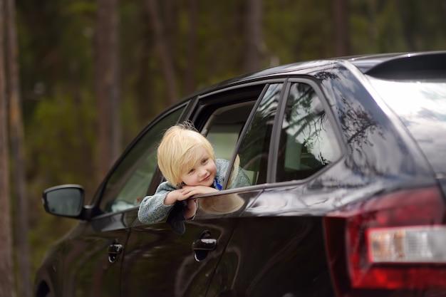 Joli petit garçon prêt pour un roadtrip ou un voyage. voyage en voiture familiale avec des enfants.