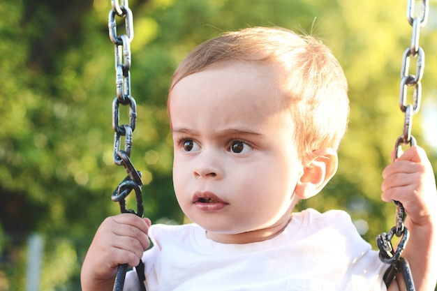 Joli petit garçon s'amusant sur une balançoire