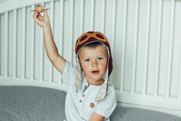 Joli petit garçon souriant dans la casquette du pilote joue sur le lit avec un petit avion en bois