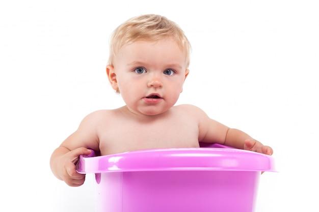Joli petit garçon timide dans une baignoire violette