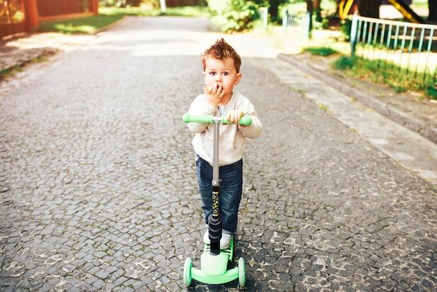 Joli petit garçon trottinette en plein air dans la rue