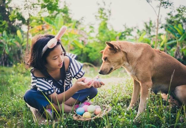 Joli petit gril portant des oreilles de lapin avec des oeufs de pâques et son chien.