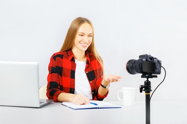 Joli sourire femme blogueuse enregistrant son contenu sur caméra. tutorat en ligne.
