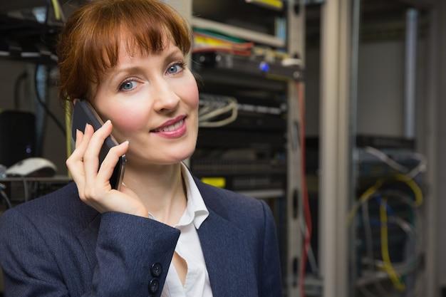Joli technicien en informatique parlant au téléphone à côté du serveur ouvert
