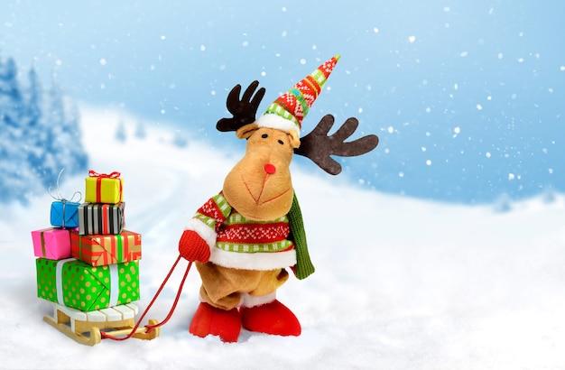Joli wapiti de noël avec des coffrets cadeaux sur le traîneau sur fond de paysage enneigé. cerf de noël avec des cadeaux.