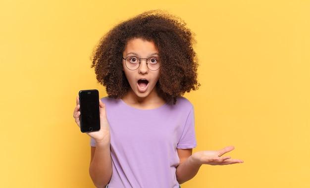 Jolie adolescente afro bouche bée et étonnée, choquée et étonnée par une incroyable surprise et tenant une cellule