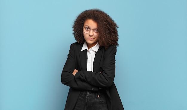 Jolie adolescente afro haussant les épaules, se sentant confuse et incertaine, doutant avec les bras croisés et le regard perplexe. concept d'entreprise humoristique