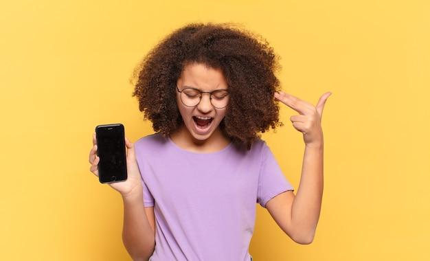 Jolie adolescente afro à la malheureuse et stressée, geste de suicide faisant signe des armes à feu avec la main