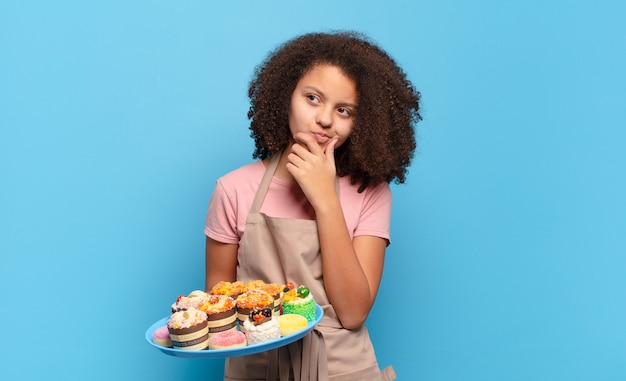 Jolie adolescente afro pensant, se sentant douteuse et confuse, avec différentes options, se demandant quelle décision prendre. concept de boulanger humoristique