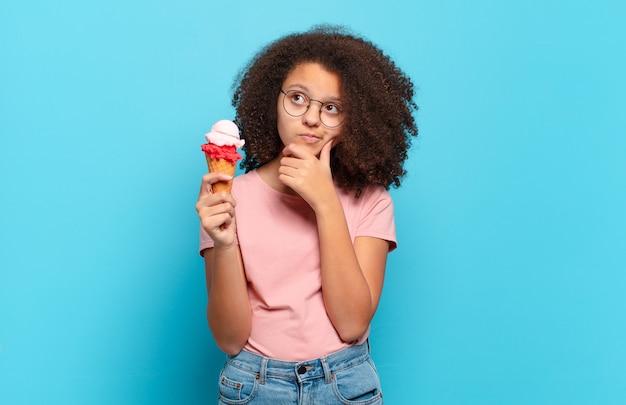 Jolie adolescente afro pensant, se sentant douteuse et confuse, avec différentes options, se demandant quelle décision prendre. concept de crème glacée sumer