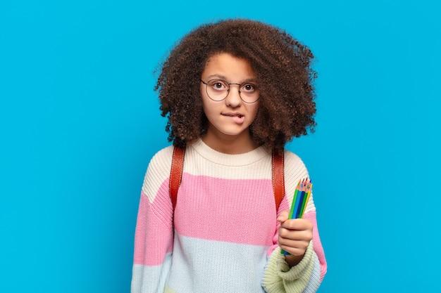 Jolie adolescente afro à la perplexité et à la confusion, se mordant la lèvre avec un geste nerveux, ne sachant pas la réponse au problème