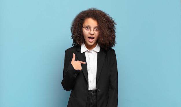 Jolie adolescente afro à la recherche de choc et de surprise avec la bouche grande ouverte, pointant vers soi. concept d'entreprise humoristique